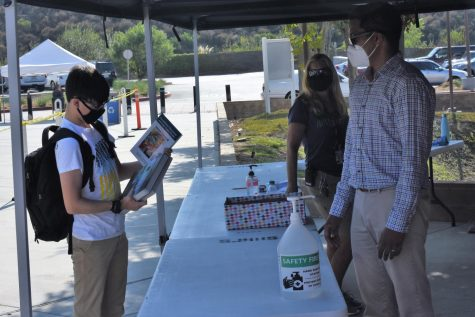 A student checks out his new textbook for the 2020-2021 school year. During textbook distribution, students and staff were required to wear masks and be socially distant from one another.