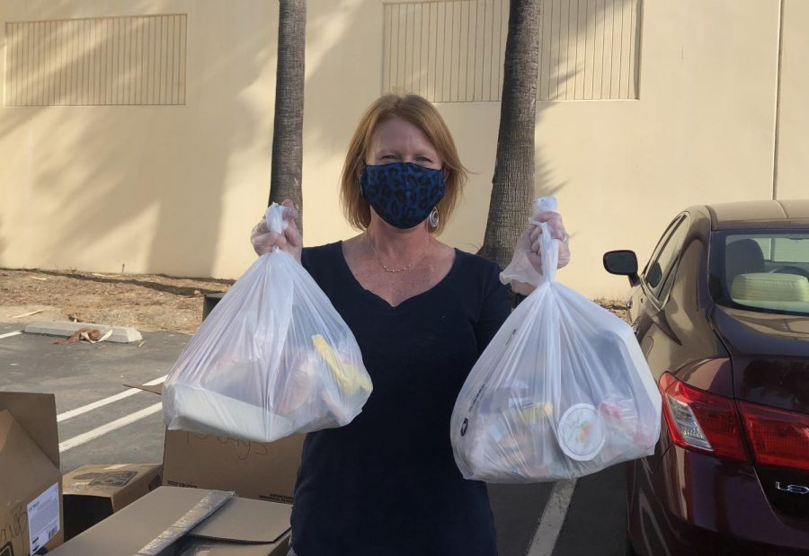 Kristin Hilleman, director of food and nutrition services of CUSD, smiles with under her mask as she holds food bags. These food bags are free for pickup at school for in person students or at the CUSD Food & Nutrition Services Office for online students. Any CUSD student can pick up these bags for free.