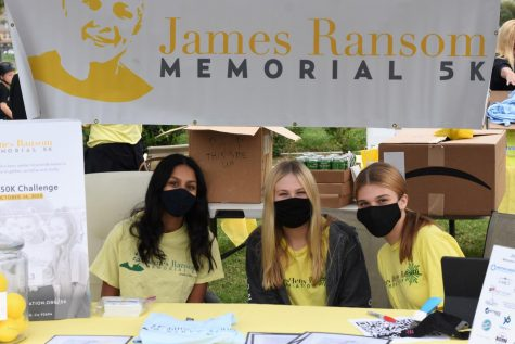 "From left to right Shruti Marada (11), Lillie Ransom (10), and Taylor Zienblach (10) help participant out by handing them their running bibs and giving them the 4th annual James Henry Ransom 5k shirt. While the run is still going on right now, on November 24th, the foundation held a ""kick-off"" day for the run."