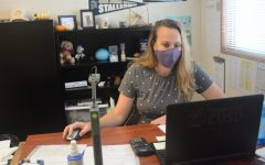 With a mask on, new Conceptual Physics teacher, Lauren Smith, works at her desk, and is getting used to her new classroom.