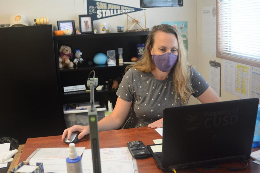 With+a+mask+on%2C+new+Conceptual+Physics+teacher%2C+Lauren+Smith%2C+works+at+her+desk%2C+and+is+getting+used+to+her+new+classroom.