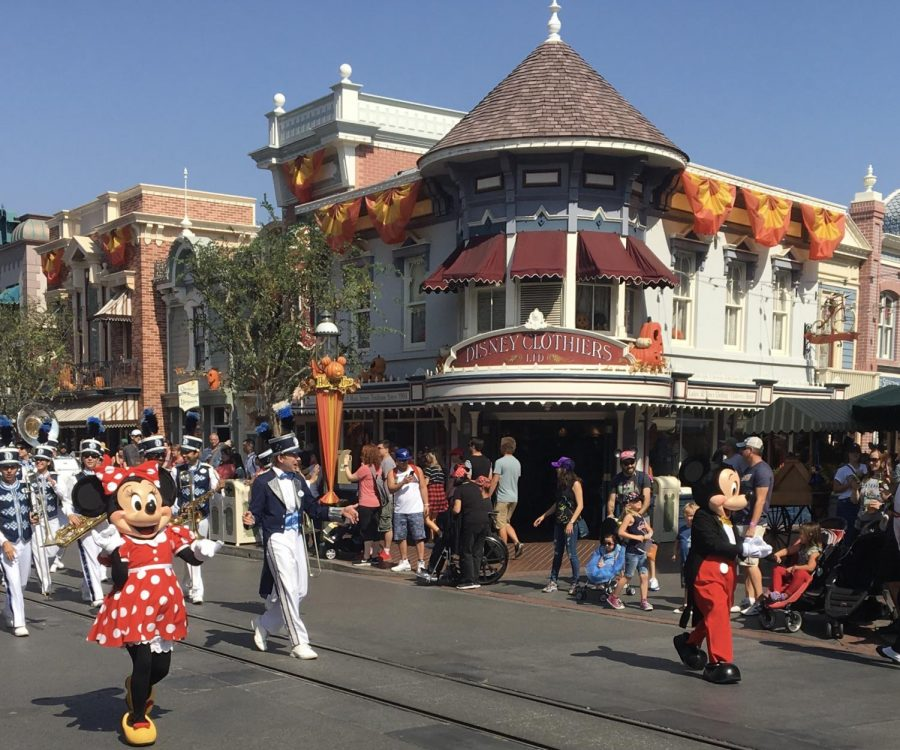 People roaming Main Street of Disneyland in California with Mickey and Minnie.