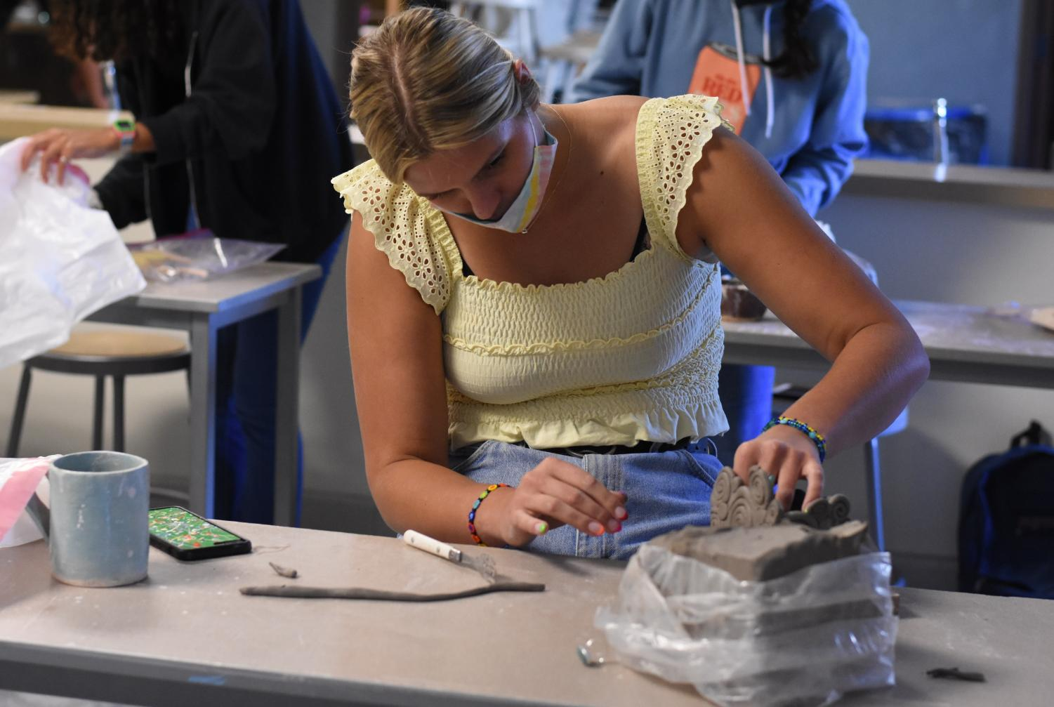 A student in the pottery elective works on her clay project. The student wears a face mask to follow CUSD