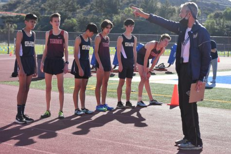 Before the meet began, cross country coach Bob Price explains to the runners what the course will be for their race. The race began on the track, the athletes would run to the teacher
