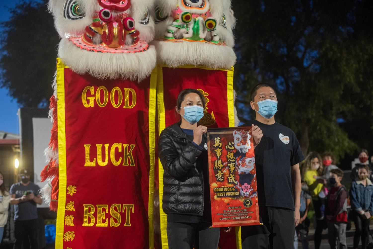 """This lantern festival was hosted to share Chinese culture and raise awareness towards anti-Asian attacks in the community. The Si family has been the latest victim of anti-Asian harassment, where teenagers threw rocks at their house and yelled racist slurs at them. Haijun Si and his wife stand in front of banners saying """"Good luck best wishes."""""""