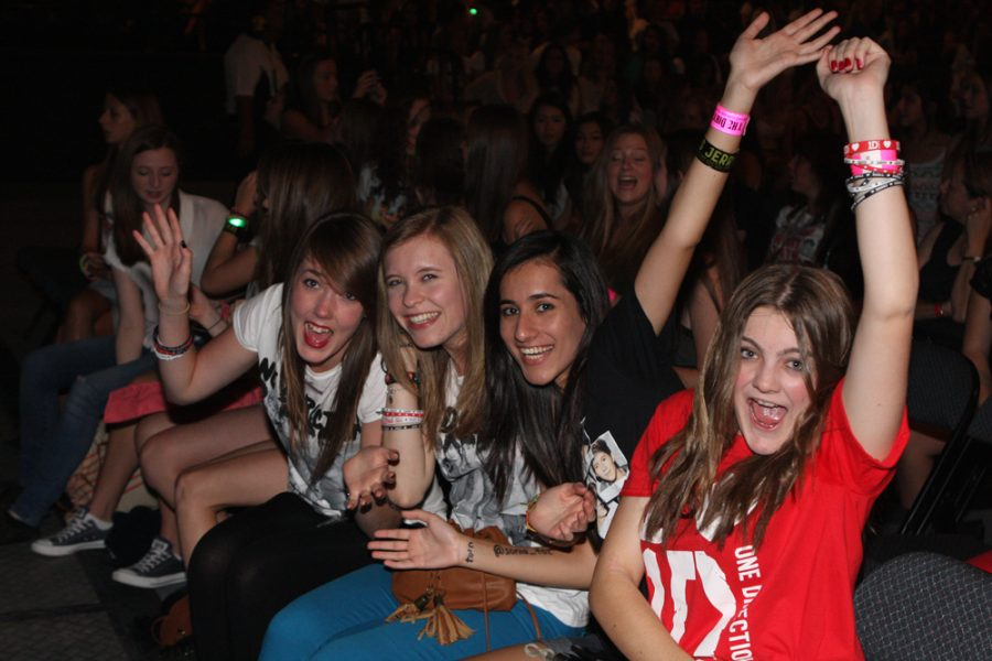Fangirls smile at a One Direction concert, dressed in the boyband's merchandise. The girls excitedly wave at the camera during the event. Fangirls receive significant criticism and are often degraded for their likes. It's time we stop associating female joy with shame, and learn to celebrate excitement.