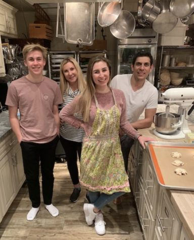 Christine and Victor Abuharoon, as well as two of their volunteers, Sofia and Jordan Votava, pose in the kitchen. While the main product is pizza dough, SMIJJ has recently began selling cookies, which can be seen on the cooking tray,