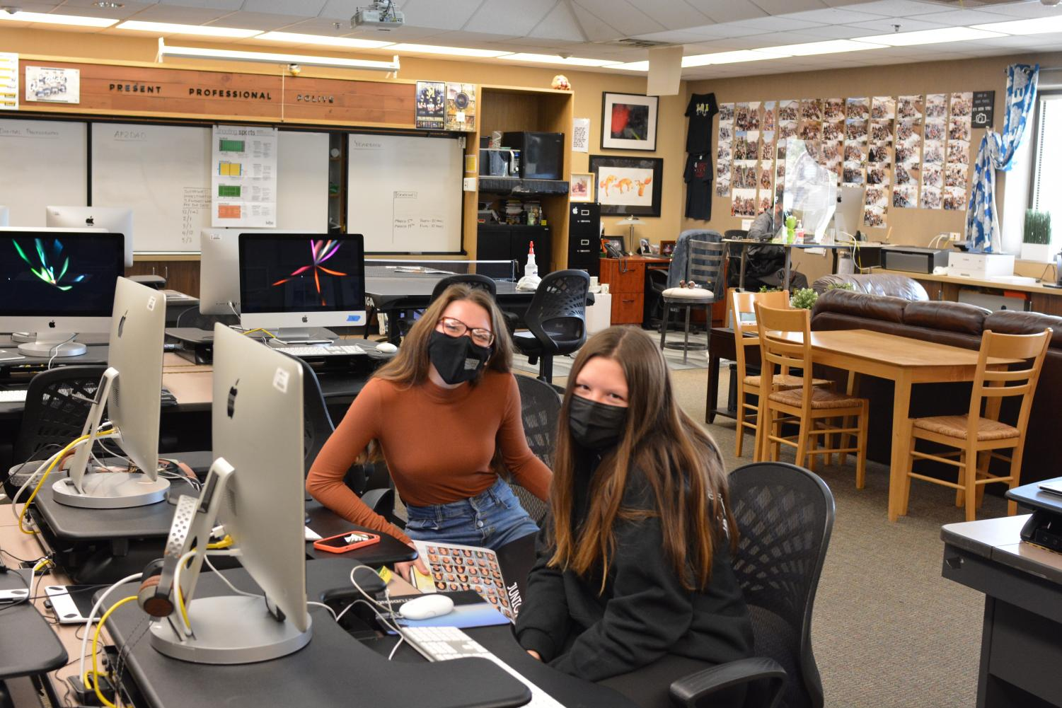 Students Jaycee Roberts (left) and Amelia Ray (right) pose while working on the yearbook during hybrid online schooling.