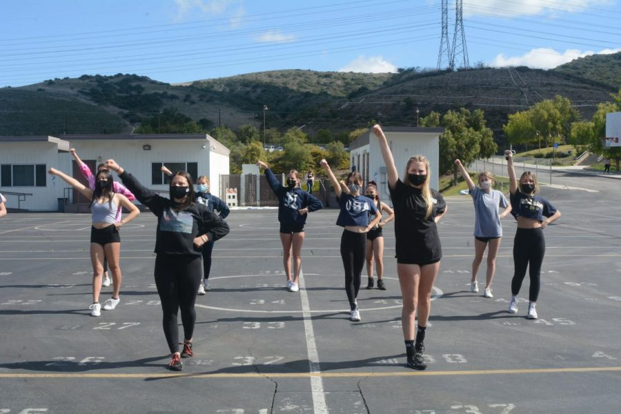 Junior Varsity cheerleaders practice on the lower basketball courts. During practice and at the games, the students are required to be both masked and distanced. Cheerleaders have been able to attend football games both at home and away and even had their own senior night along with the football team.