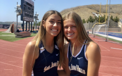 Haley Juarez (10) and Ashley Petersen (9) taking team pictures as track season comes to an end, one of the last times this school year wearing their uniform.