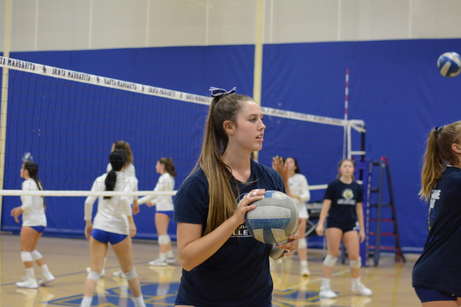 Cat Conlisk (12), practices with teammates at an away game against Santa Margarita high school. Just weeks ago, Conlisk committed to Seattle University, where she will continue pursuing volleyball with a brand new group of players.