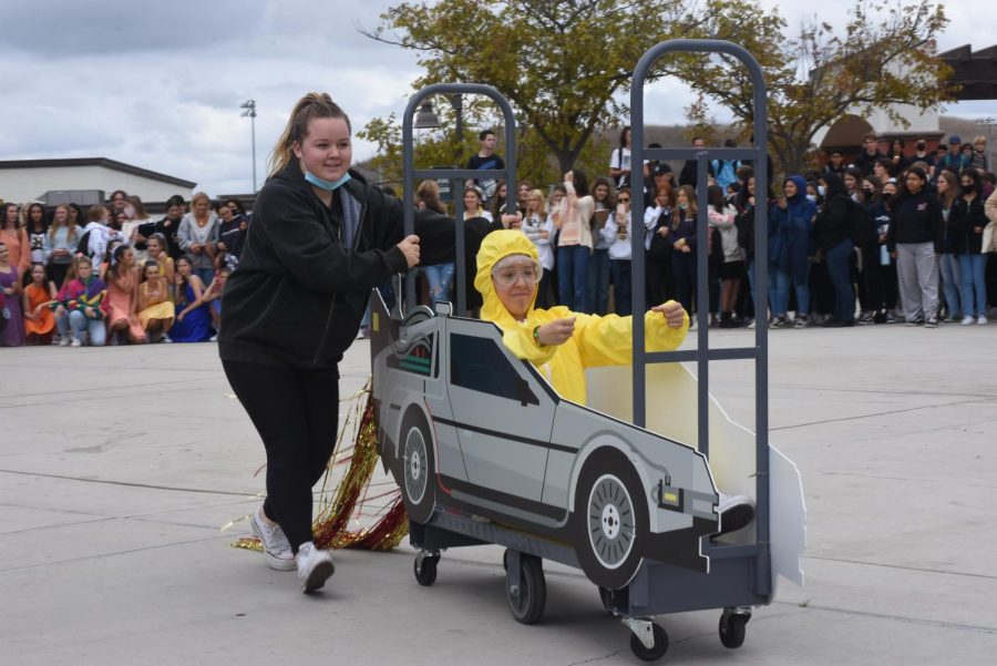 """Crew member Sydney Briggs (9) and dancer Cali McCanna (12) perform at the lunchtime pep rally with the theme """"Back to the Future."""" Although dance had originally planned to perform their pep rally show on the football field, the weather had other plans. Fortunately, they were able to seamlessly transition the production to the quad by lunch time. While the change was disappointing, the group was later able to perform on the field again at the football pregame."""
